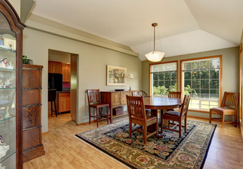 Traditional dining room interior with rug and big windows.