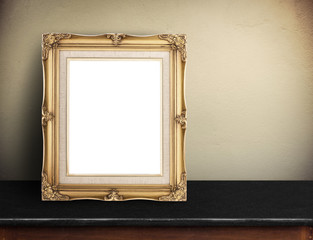 Blank Gold victorian picture frame on black marble table at yell