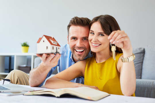 Happy couple holding keys to new home and house miniature