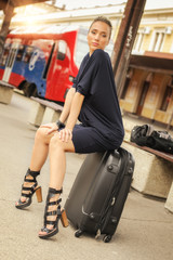 Elegant woman sitting on suitcases on the railway station