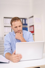 mann im büro schaut nachdenklich auf seinen laptop