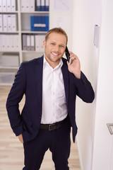 geschäftsmann steht in seinem büro und telefoniert