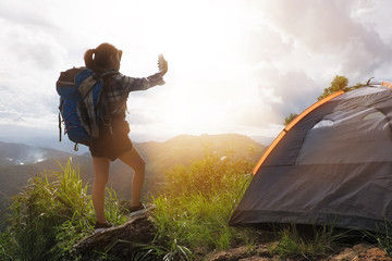 A woman use smartphone take a photo sunrise in Camp on the mount