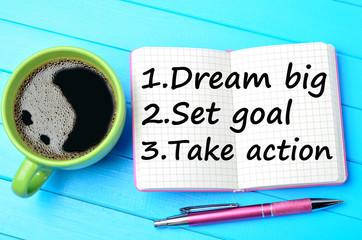 Dream big Set goal Take action on notepad