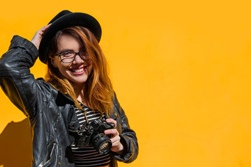 Hipster fashionable teenage girl wearing black leather jacket and black beanie hat with old camera.Yellow background.Free space.Smile