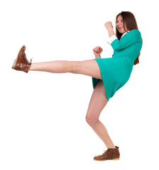skinny woman funny fights waving his arms and legs. Isolated over white background. Long-haired brunette in a green dress fights feet.