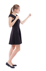 skinny woman funny fights waving his arms and legs. Isolated over white background. Blonde in a short black dress in a boxing rack.
