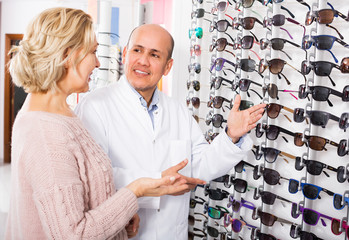 Male optician offering glasses frames