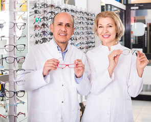 opticians helping to choose glasses in modern optics store