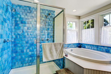 Bathroom interior with blue tile trim. View of bathtub and shower