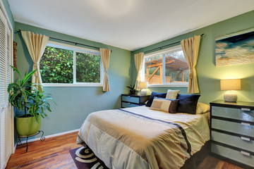 Blue bedroom interior with king size bed, hardwood flooe and beige curtains