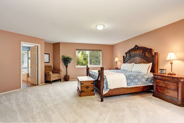 Bedroom interior with carved wooden furniture and carpet floor.