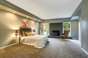 Spacious bedroom interior with brick fireplace and and white bedding