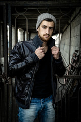 Bad boy concept. Portrait of brutal young man with short hair wearing black jacket and gray hat , Hipster style. Copy-space. Outdoor shot