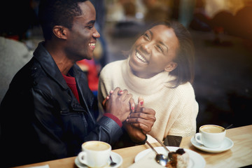 Cheerful happy lovers enjoying leisure while sitting in bar in cold winter day