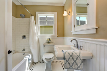 American bathroom interior in white tones and tile floor.