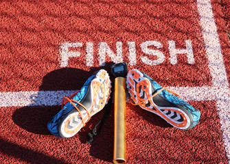 racing spikes a baton and a stop watch placed on the finish line