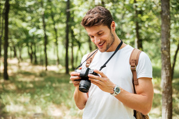 Smiling man photographer using modern photo camera in forest