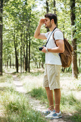 Man photographer using camera and looking far away in forest