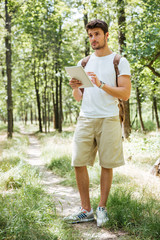 Full length of man with backpack using tablet in forest