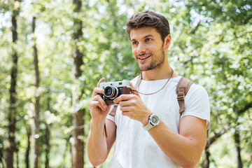 Happy man taking pictures with old photo camera in forest