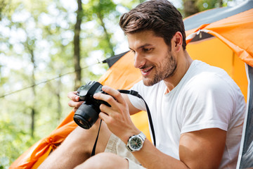 Man tourist taking photos with modern photo camera in forest