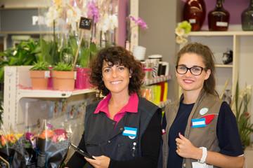 Happy smiling florist women at flower shop counter