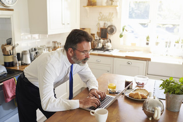 Man in shirt and tie stands working on laptop in kitchen