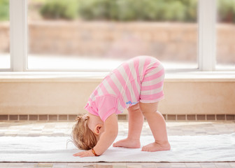 Portrait of cute adorable white Caucasian baby girl doing physical fitness exercises yoga alone standing on floor in swimming pool