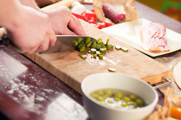 Mens hands cut pizza ingredients on bamboo cutting board for cooking pizza.