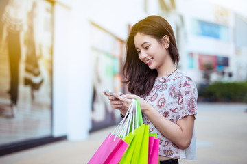 Happy young woman using cell phone at a shopping center,high key