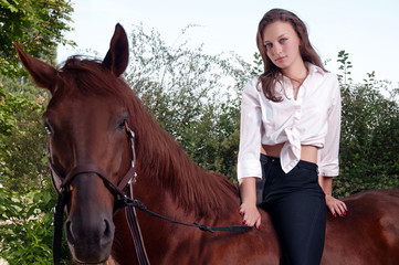 beautiful young woman riding a horse