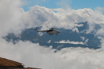 Helicopter with cargo cable and mountains in clouds