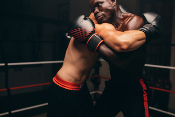 Male fighters in darkened gym grapple one another