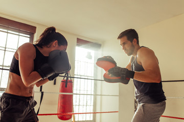 Female pugilist exercises with instructor