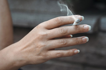 woman holding burning cigarette in hand. smoking woman