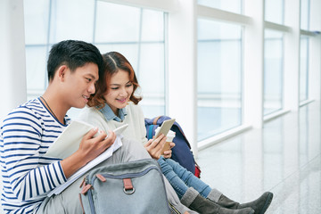 Vietnamese couple sitting on university floor and reading book