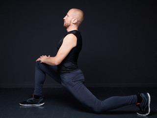Young fitness man performing stretching of the thigh quadriceps, doing forward lunge