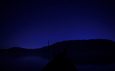 Stargazer on dock in lake, under night sky with stars