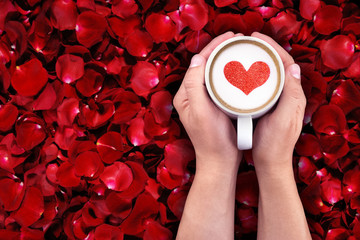 man holding hot cup of milk on red rose petals background, with red heart shape