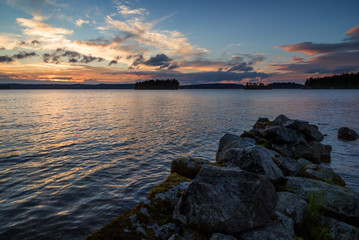 View of an old and broken pier made of rocks and lake at sunset in Finland in the summer.