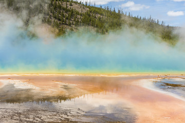 Rising blue steam and mist from hot spring in Midway Geyser basin at Yellowstone National Park with red bacterial patterns