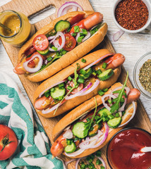 Homemade hot-dogs on wooden serving board with fresh vegetables, spices, ketchup and mustard over white painted background, top view