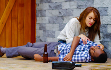 Man wearing casual clothes lying drunk passed out on wooden surface, pretty woman sitting beside him trying to get contact by touching and shaking