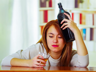 Woman wearing white sweater sitting by bar counter lying over desk holding glass and bottle to head, drunk depressed facial expression, alcoholic concept