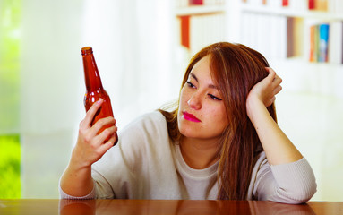 Woman wearing white sweater sitting by bar counter lying over desk staring at beer bottle, drunk depressed facial expression, alcoholic concept