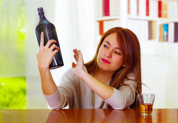 Woman wearing white sweater sitting by bar counter lying over desk next to glass and bottle, drunk depressed facial expression, alcoholic concept