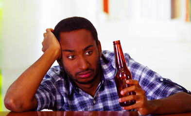 Handsome man wearing white blue shirt sitting by bar counter lying over desk holding brown beer bottle, drunk depressed facial expression, alcoholic concept
