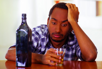 Man wearing blue white shirt sitting by bar counter holding whiskey glass next to liquor bottle, depressed facial expression