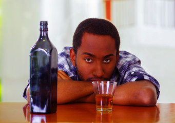 Man wearing blue white shirt sitting by bar counter lying over desk next to glass and bottle, depressed facial expression